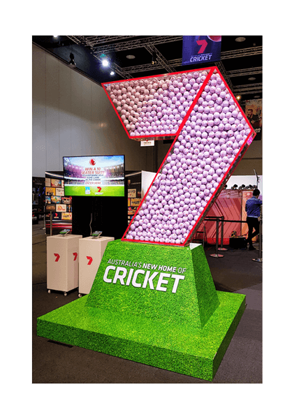 Giant 7 shaped container with cricket balls inside.